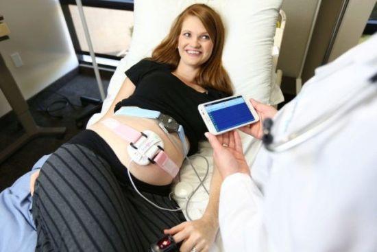 У беременной слушают сердцебиение плода