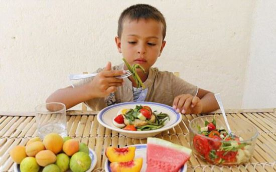 Ребенок ест салат и фрукты