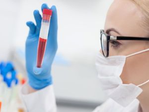 Лаборант смотрит на пробирку с кровью
