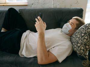 Человек в маске на диване