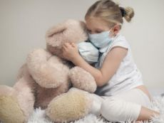 Девочка в маске обнимает мишку